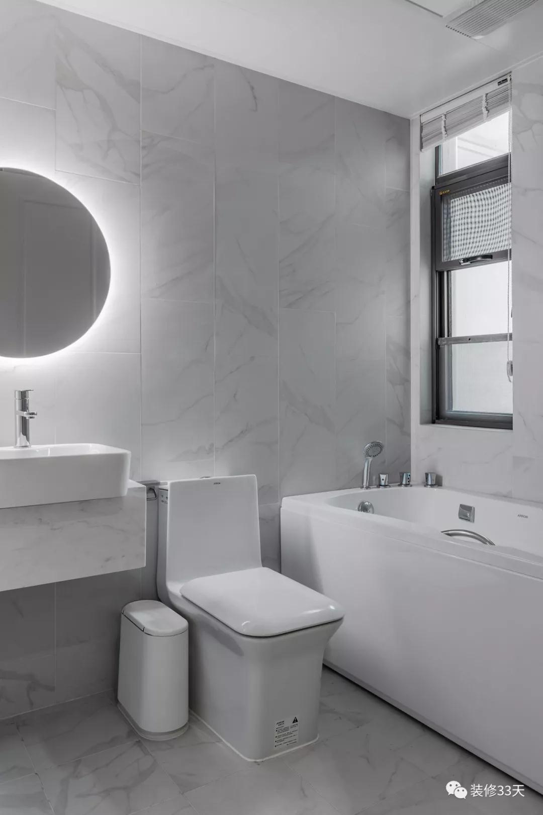 卫生间整体竖贴浅灰色石纹瓷砖,悬挂式台盆柜点缀自带光源的墙镜